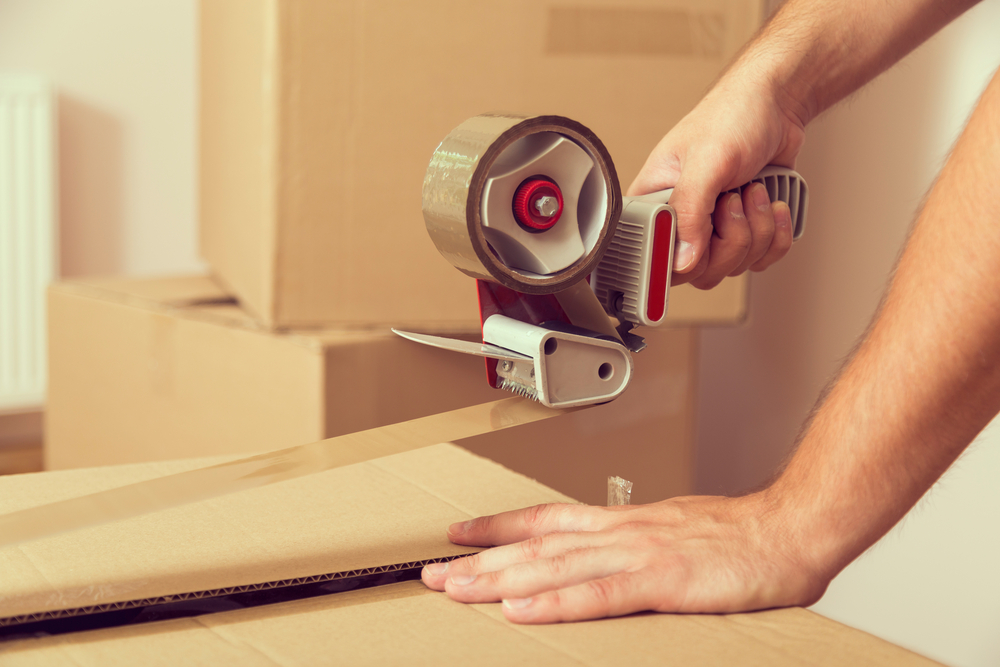 A photograph of a man taping a cardboard box shut.