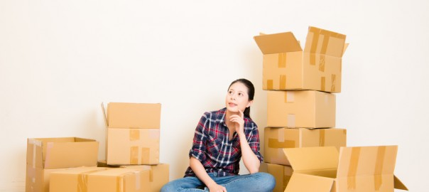 A woman sitting in front of several cardboard boxes looking inquisitive.