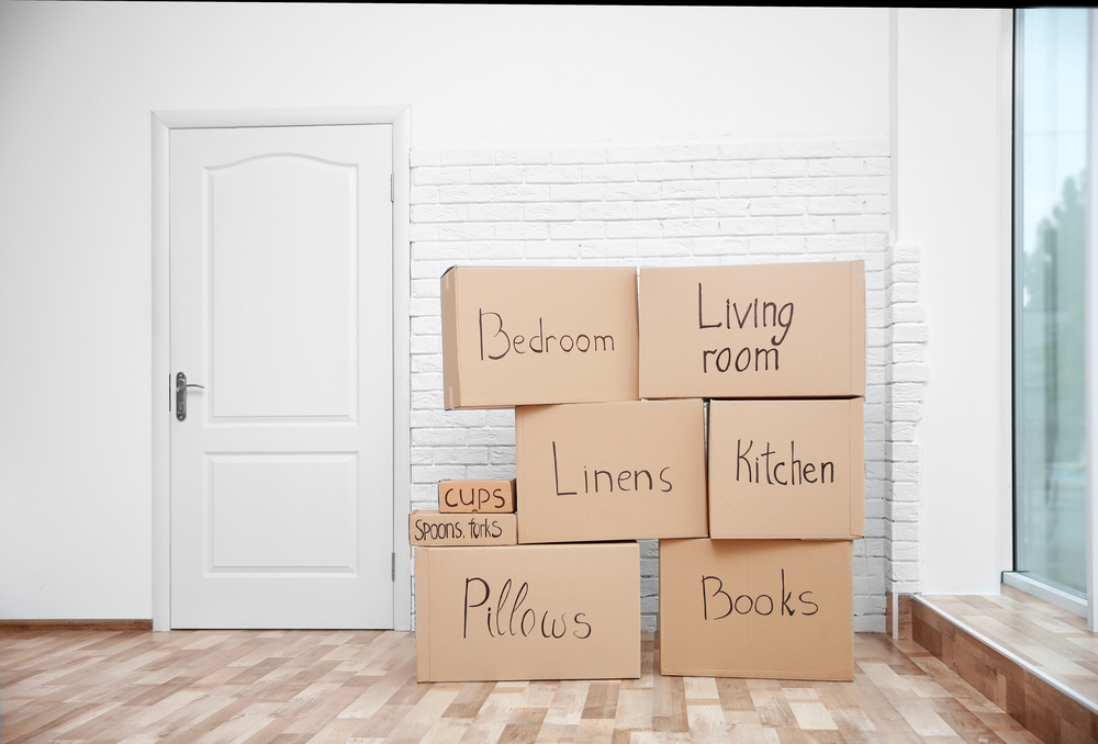A photograph of moving boxes stacked in the corner of a room.