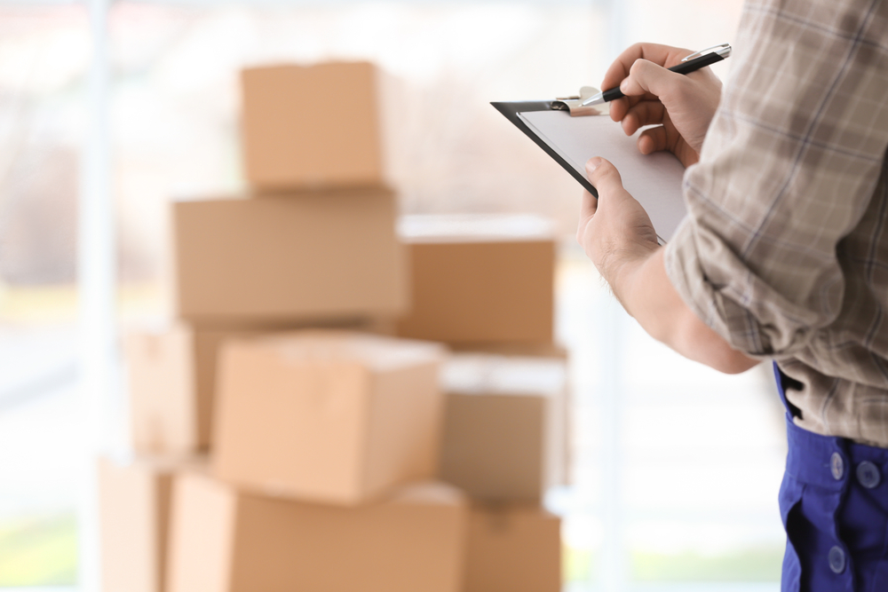 A photograph of a man filling out a checklist with packed boxes in the background.