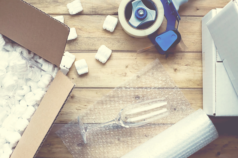 A photograph of a fragile glass being packed with care.