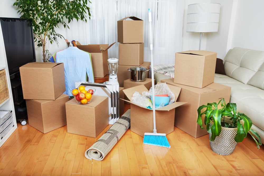 A photograph of boxes sitting in the living room of an apartment on move-in day.