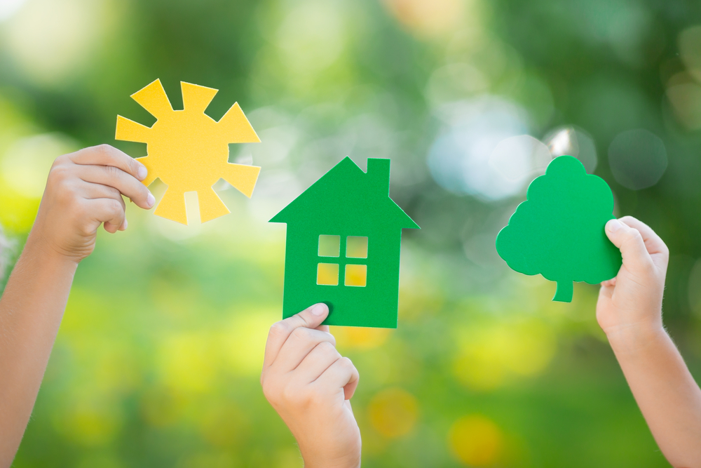 A photograph of hands holding up paper cut outs of the sun, a house, and a tree amidst a spring backdrop.
