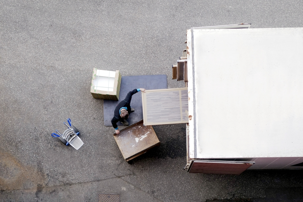An aerial photograph of a moving professional removing boxed items from a moving truck.